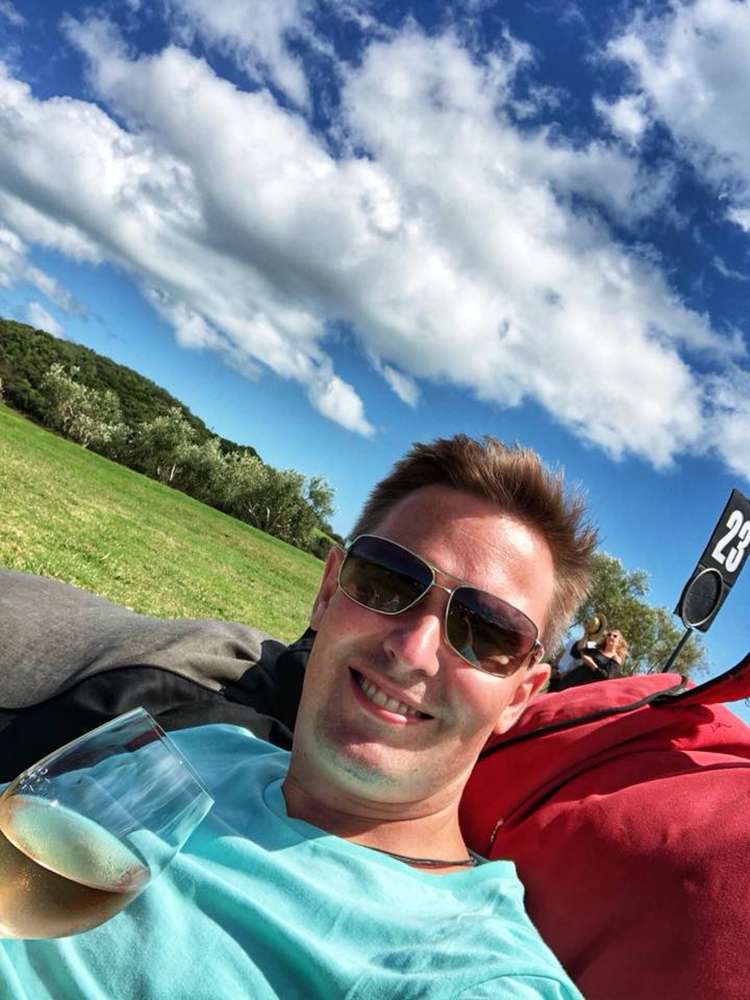 Yury on a beanbag in the grass with a glass of white wine at Cable Bay vineyard in Auckland, New Zealand