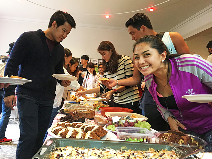Students from many countries serving themselves from a long table full of international food