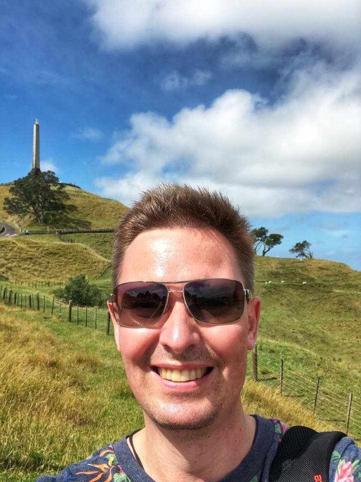 Yury taking a selfie with One Tree Hill in the background (Auckland, New Zealand)