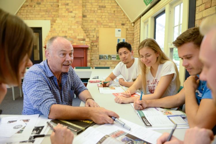 Multicultural class of students learning English in Auckland, New Zealand with their teacher Peter